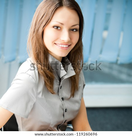 Young happy smiling cheerful business woman at office, with copyspace - stock photo