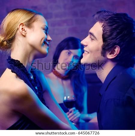 Young happy smiling couple and woman looking at them at club. Focus on couple. Love, party and date concept.