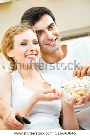 Young happy smiling couple eating popcorn and watching TV together at home. Love, relations, romantic concept shoot.