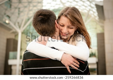 Young happy smiling couple in embracement - outdoor on street - stock photo