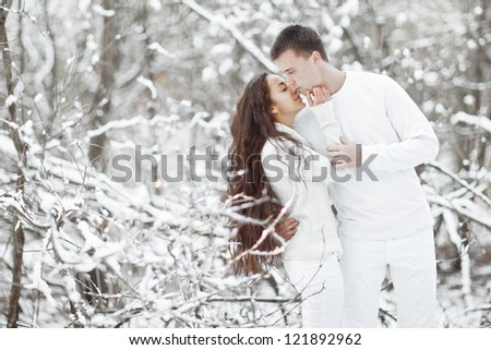 Young happy smiling couple in winter forest - stock photo