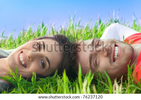 Young happy smiling couple looking at camera lying in the grass outdoor - stock photo