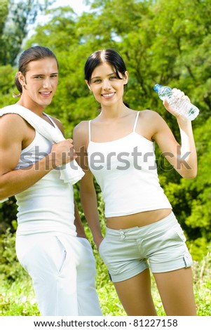 Young happy smiling couple with bottle of water in sport wear on workout, outdoors - stock photo