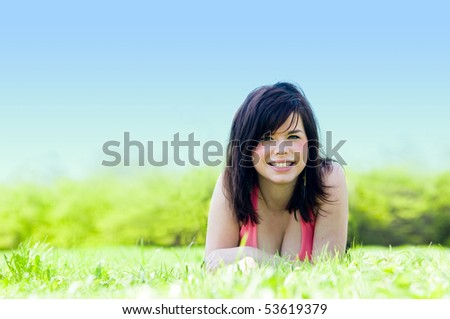 Young happy smiling girl lying on grass - stock photo