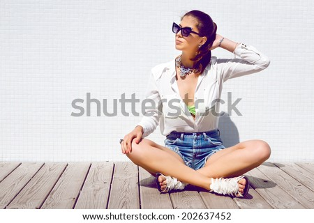 Young happy smiling girl sitting outdoor in wooden floor, smiling and having fun alone on her vacation in stylish bright summer clothes. - stock photo