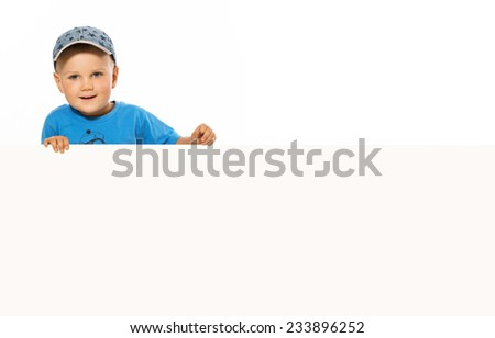 young happy smiling little boy look outs from the blank billboard. - stock photo