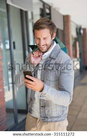 Young happy smiling man holding shopping bags and looking at his mobile in front of a store