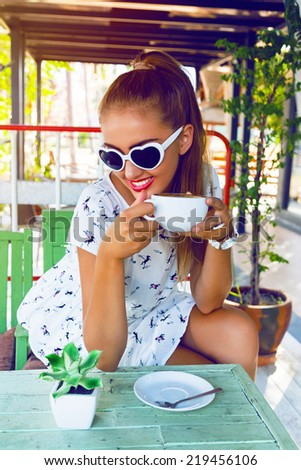 Young happy smiling petty girl, enjoy her morning coffee alone at her favorite cafeteria. Wearing retro white dress and cute vintage heart sunglasses, have bright lipstick and ponytail.  - stock photo