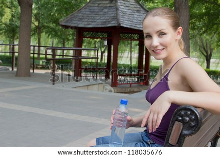 Young happy smiling sport fitness woman resting after exercise outside on summer. Girl sitting on bench in green park and holding a bottle of cold water in her hand - stock photo