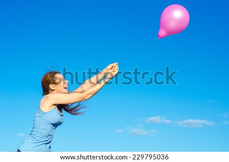 Young happy smiling woman arms raised holding pink flying air balloon day light blue sky background. Positive emotion face expression feeling life perception. Life joy freedom wellness nature concept - stock photo