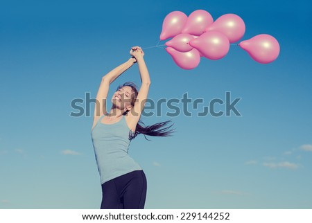 Young happy smiling woman arms raised holding pink flying balloons on daylight blue sky background. Positive emotions face expression feelings life perception. Life joy freedom wellness nature concept - stock photo