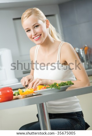 Young happy smiling woman cooking salad at home