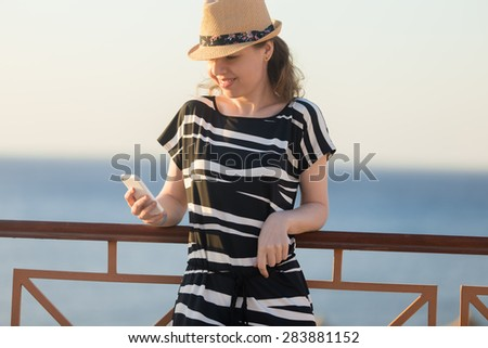 Young happy smiling woman in cute straw hat and casual summer dress leaning on railing on sunny street of sea town, holding cellphone, looking at screen, using app, messaging - stock photo