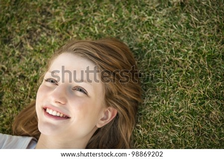 Young happy smiling woman lying in grass - above view with copy space - stock photo
