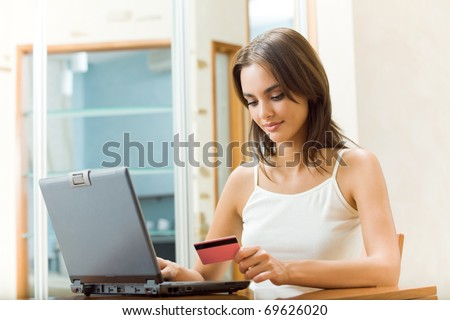 Young happy smiling woman paying by plastic card, at home