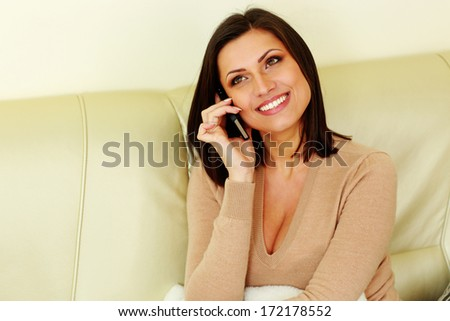 Young happy smiling woman talking on the phone - stock photo