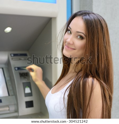 Young happy smiling woman using cash machine - stock photo