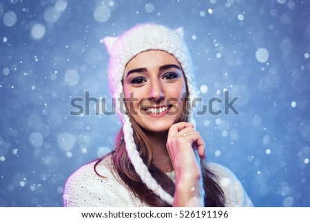 Young happy smiling woman winter portrait with snow on blue background