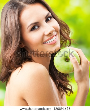 Young happy smiling woman with apple, outdoors - stock photo