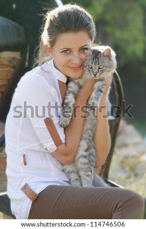 young happy smiling woman with cat on natural background - stock photo