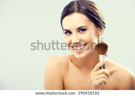 Young happy smiling woman with cosmetics brush, with empty blank copyspace area for slogan or text - stock photo