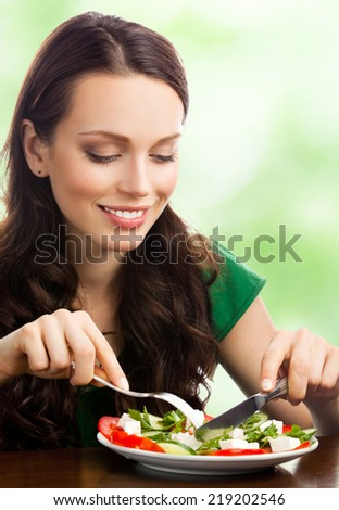 Young happy smiling woman with fegetarian salad, outdoor - stock photo