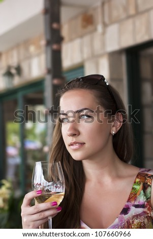 Young happy smiling woman, with glass of whitewine at restaurant - stock photo