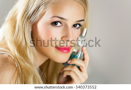 Young happy smiling woman with perfum bottle indoors. Beauty and fashion concept.