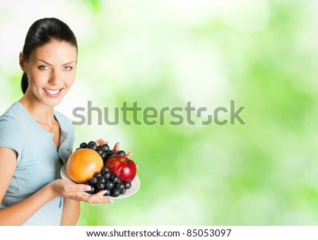 Young happy smiling woman with plate of fruits, outdoor. You can use right part for slogan, big text or banner. - stock photo