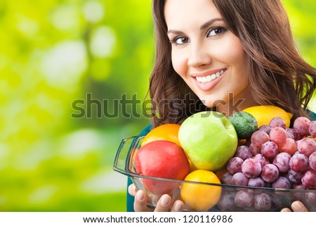 Young happy smiling woman with plate of fruits, outdoors, with copyspace for text or slogan. - stock photo