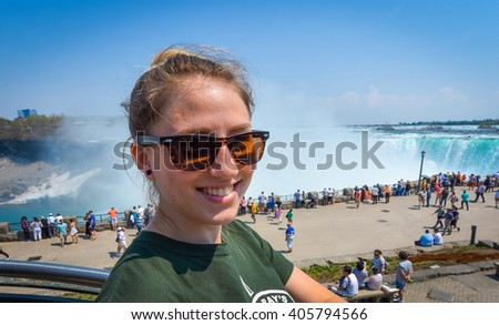 Young happy smiling woman with sunglasses on beautiful sunny springtime morning at Niagara Falls.  People & tourists in background see, hear, and feel the power of the Falls. - stock photo