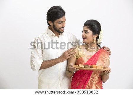Young happy south Indian couple holding cookies and sweets for Indian festival on white. - stock photo