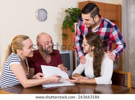 Young happy spouses sitting with documents and asking friends for advice