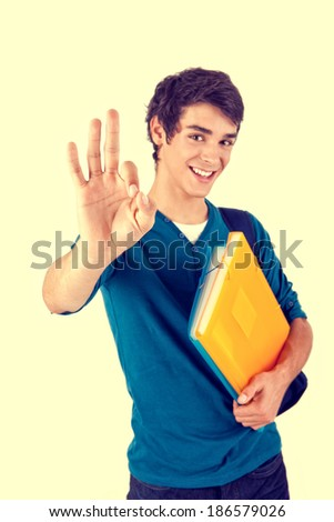 Young happy student carrying books on white background