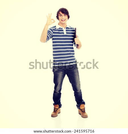Young happy student man with notebook gesturing perfect - stock photo