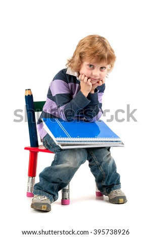 Young happy student seated in a chair with big pencils isolated in white