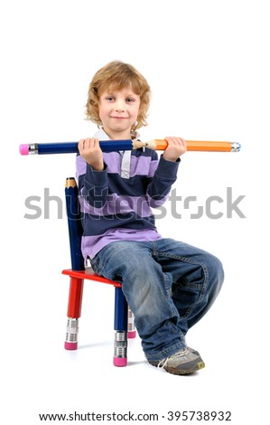 Young happy student seated in a chair with big pencils isolated in white - stock photo