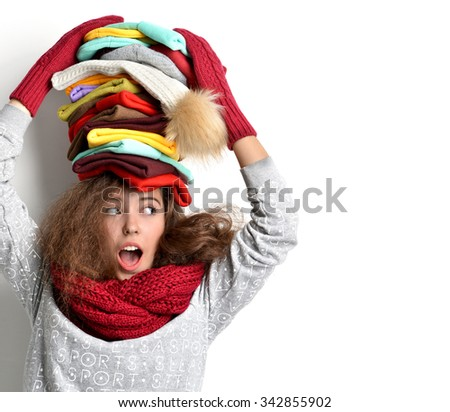 Young happy surprised girl with many warm winter hats in different colors with text copy space looking at the corner on white background - stock photo