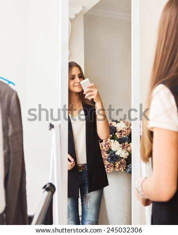 Young happy teen girl making photo with mobile camera in shop - stock photo