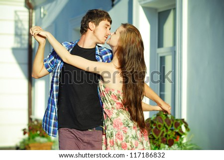 Young happy teenage couple beautiful woman & handsome man dancing passionately outdoors - stock photo