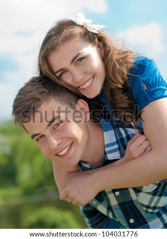 Young happy teenage couple in love against blue sky