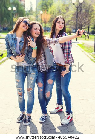 Young happy teenage girls making selfie and having fun in summer park. - stock photo