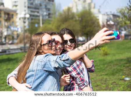 Young happy teenage girls making selfie and having fun in summer park.