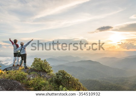 Young happy tourist on top of a mountain enjoying valley view - stock photo