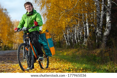 Young happy tourist standing with his loaded bicycle on an autumn road