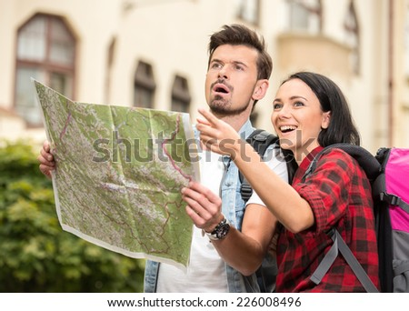 Young happy tourists is sightseeing city with map. - stock photo