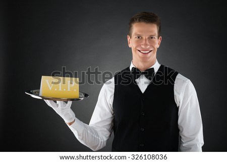 Young Happy Waiter Showing Vip Sign On Tray - stock photo