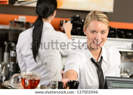 Young happy waitress cashier giving coffee in cafe