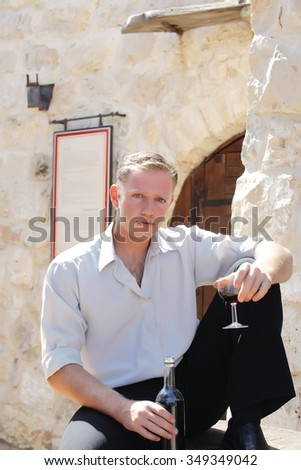 young happy white Caucasian man taste and enjoy red wine outdoor in in countryside . classic style fashion. - stock photo