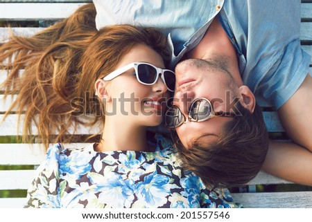 Young happy woman and her handsome boyfriend laying outdoor in wooden white floor, wearing vintage styled clothes and sunglasses. - stock photo